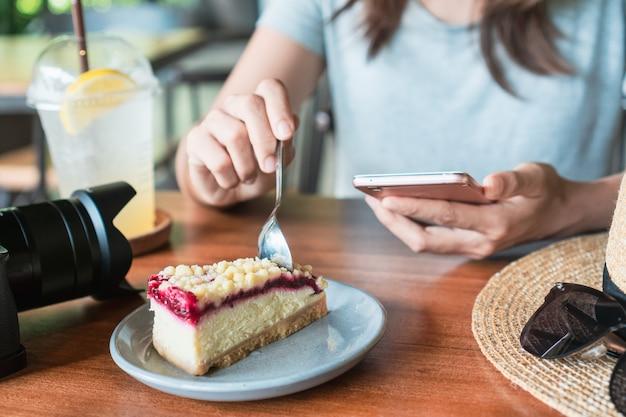 カフェでケーキを食べながら携帯電話を保持している女性の手のクローズアップ。