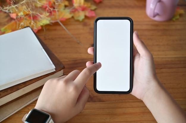 빈 화면으로 휴대 전화를 들고 여자의 손을 클로즈업합니다. 프리미엄 사진