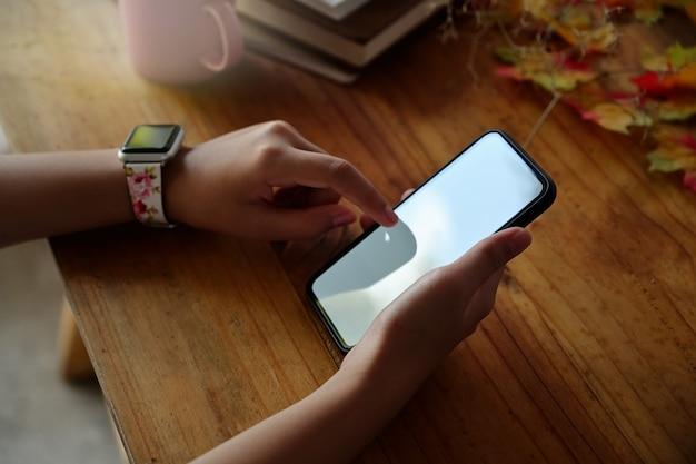 빈 화면으로 휴대 전화를 들고 여자의 손을 클로즈업합니다.