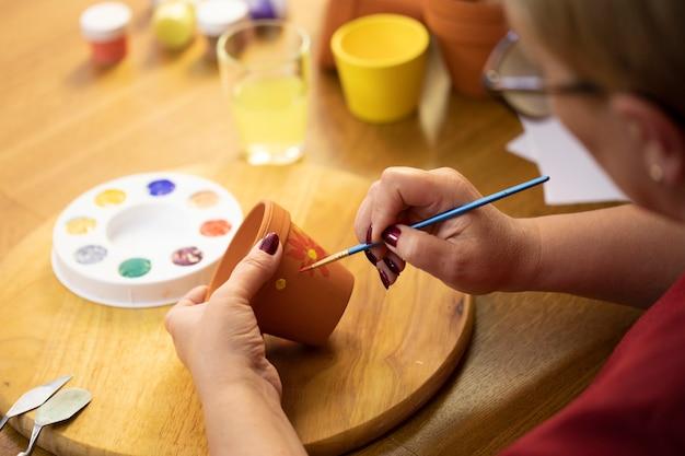 図面の趣味の塗料でフラワーポットを描く女性の手のクローズアップ