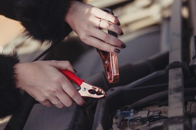 Крупный план женских рук с электрическими зарядными клеммами под капотом автомобиля