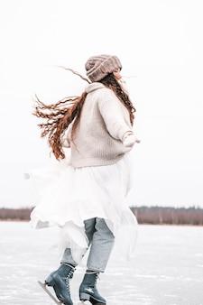 Крупным планом женские ноги на коньках зимой на открытом катке.