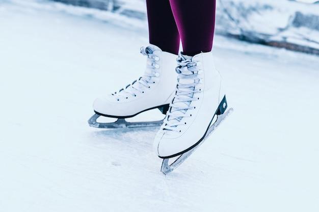 オープンスケートリンクで冬のスケートの女性の足のクローズアップ。