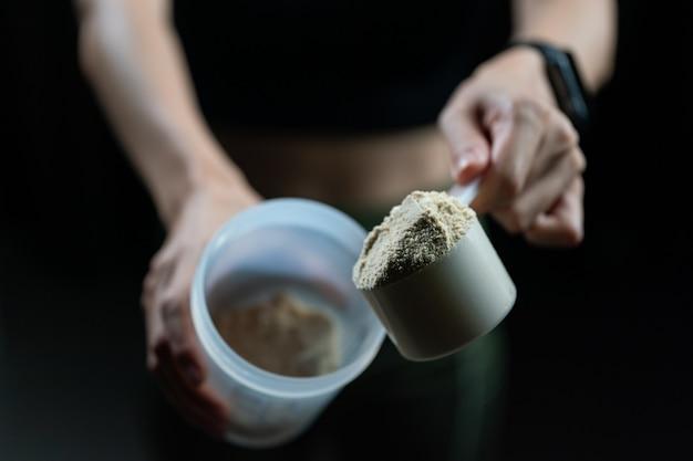 Крупным планом женщины с мерной ложкой сывороточного протеина и шейкер, готовят протеиновый коктейль.