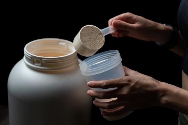 Крупным планом женщин с мерной мерной ложкой из банки сывороточного протеина и бутылкой шейкера, готовящей протеиновый коктейль