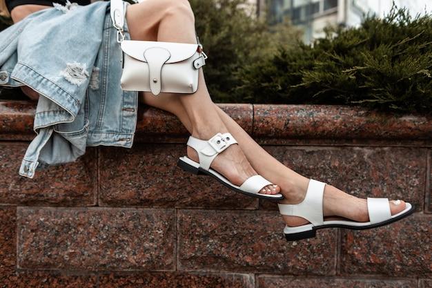 거리에 흰색 세련된 핸드백이 달린 세련된 가죽 여름 신발에 여자 다리의 클로즈업.