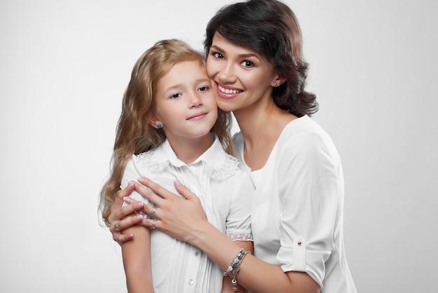 素敵な家族のカップルのクローズアップ:美しい母親と彼女の小さな素敵な娘。彼らはかわいい笑顔でとても幸せです。彼らは白いtシャツを着ています。