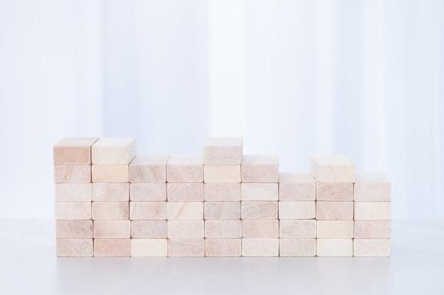 白い日光の背景に木製のブロックのクローズアップ。安定性の概念。