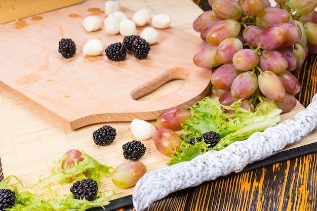 Закройте деревянные доски с сыром боккончини, вяленым мясом и свежими фруктами на деревенском деревянном столе с деревянным зерном