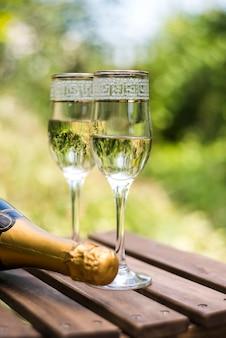 Крупным планом деревянный ящик с бокалами шампанского на открытом воздухе