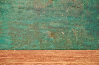 Close-up of wooden floor and green wall