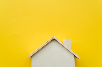 Close-up of wooden miniature house model on yellow background