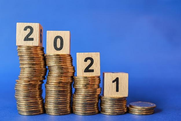 Закройте деревянный блок номер 2021 на вершине стопки золотых монет