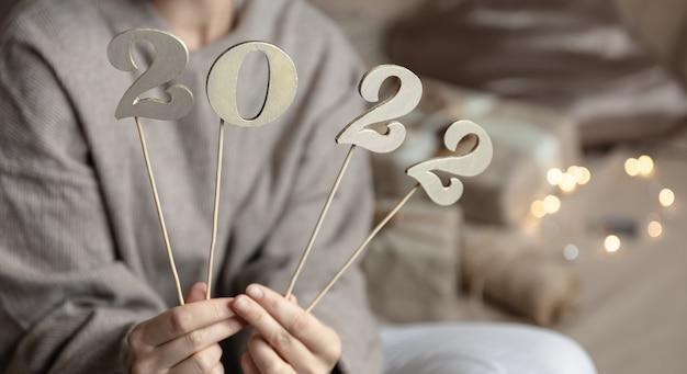ボケ味のぼやけた背景に女性の手の棒に木製の数字2022のクローズアップ。