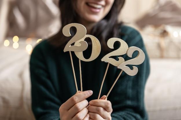 흐릿한 배경에서 한 소녀의 손에 있는 막대기에 있는 나무 숫자 2022의 클로즈업.