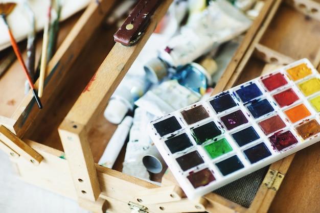 Закройте вверх деревянного художника чемодана с краской акварели, щетками и художническими инструментами. концепция искусства