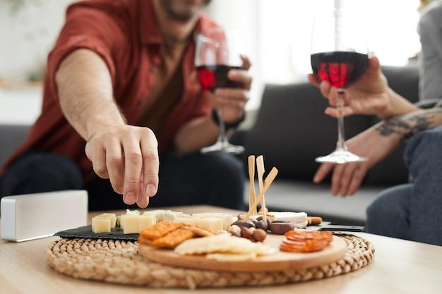 ワインを飲むカップルとテーブルの上のさまざまな種類のチーズと木製トレイのクローズアップ