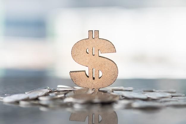 コインの山に木製の米ドル記号のクローズアップ
