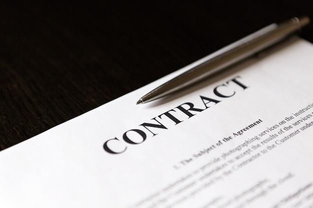 은색 펜으로 단어 계약의 클로즈업입니다. 선택적 초점.