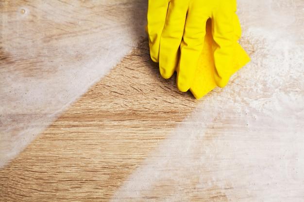 Крупным планом руки работника, вытирая пыль в офисе в желтых перчатках