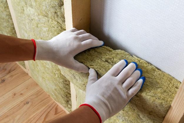 Конец-вверх рук работника в белых перчатках изолируя штат изоляции каменной ваты в деревянной рамке для будущих стен для холодного барьера.