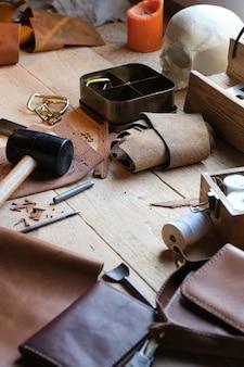 작업장에서 목수의 탁자에 있는 작업 도구와 가죽 직물의 클로즈업