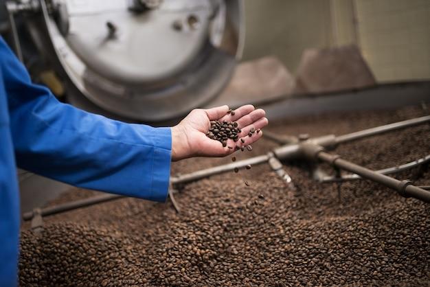 볶은 커피의 품질을 확인하는 노동자의 클로즈업. 로스팅 장비에서 작업하는 커피 로스터.