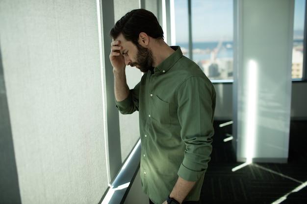 Крупным планом обеспокоенного делового руководителя, стоящего у окна в офисе