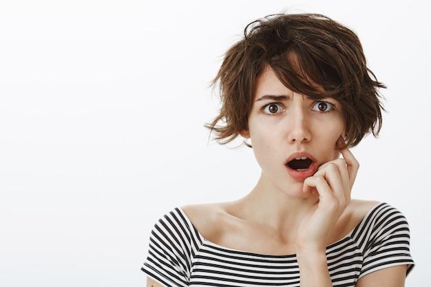 眉をひそめている心配しているあえぎの女性のクローズアップ、衝撃的なニュースを見つける