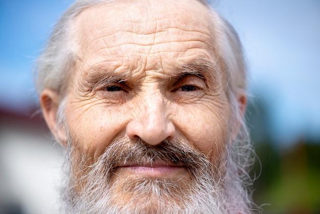 클로즈업 - 흰 머리와 흰 수염을 가진 노인 초상화의 주름진 얼굴이 심각해 보입니다.