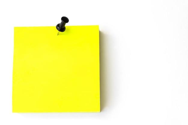Крупный план желтых клейких заметок с черной булавкой на белом фоне. желтое напоминание