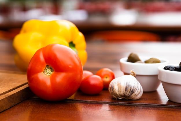 黄ピーマンのクローズアップ。トマト;ニンニクの球根と木製のテーブルにオリーブのボウル