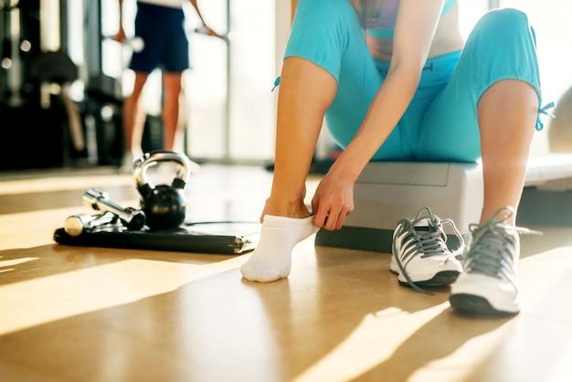 Закройте молодой активной фитнес-девушки, снимающей носок, сидя на степпере в солнечном тренажерном зале.