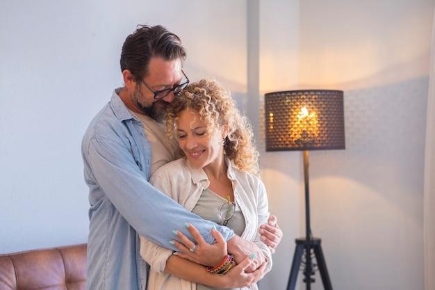 自宅で愛を抱き締める若い大人のカップルのクローズアップ-愛情を抱き合う関係で一緒に人生の成熟した人々-新しい家の男性と女性の概念