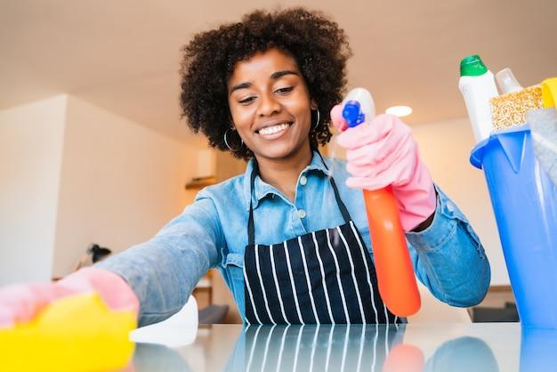 新しい家で掃除している若いアフロ女性のクローズアップ。ハウスキーピングとクリーニングのコンセプト。