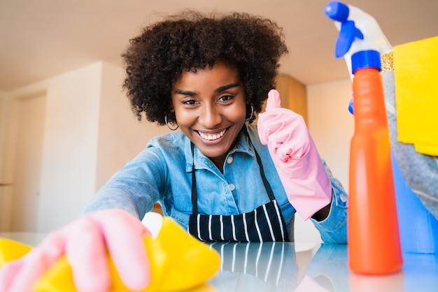 새 집에서 청소하는 젊은 아프리카 여자 닫습니다. 가사 및 청소 개념.