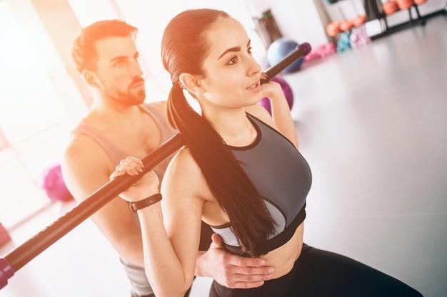 체육관에서 운동하는 젊고 아름다운 소년과 소녀의 클로즈업. 그녀는 트레이너가 그녀를 지원하는 동안 바디바를 사용하여 일부 스쿼드를 수행하고 있습니다. 컷 뷰