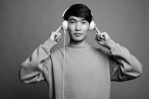 Крупным планом молодого азиатского человека, слушающего музыку