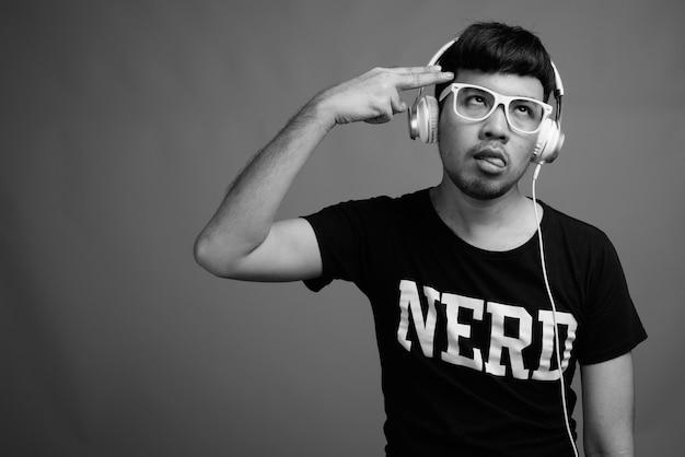 Крупным планом молодой азиатский ботаник в очках во время прослушивания музыки