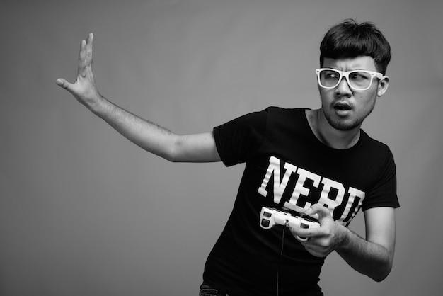 ゲームをしながら眼鏡をかけている若いアジアのオタク男性のクローズアップ