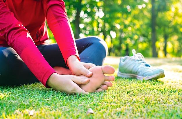 Крупным планом - молодая азиатская спортивная женщина испытывает боль в мышцах и суставах во время упражнений на открытом воздухе, во время тренировок или бега и концепции спортивной травмы
