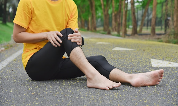 若いアジアのスポーツマンのクローズアップは、屋外運動中、トレーニングやランニング、スポーツ傷害の概念を超えて、筋肉や関節に痛みがあります