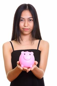 Крупным планом молодой азиатской девочки-подростка, держащей копилку