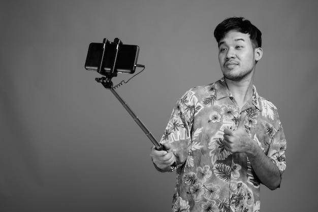 Крупным планом молодого азиатского туриста в гавайской рубашке, готового к отпуску