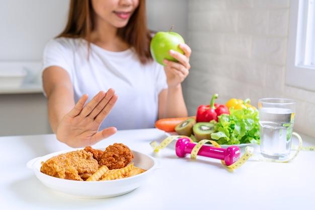 手を使って若いアジアの女性のクローズアップは、ジャンクフードを押し出し、健康食品を選択します。