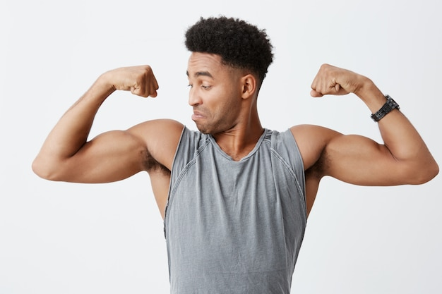 集中して自信を持って顔の表情で彼の筋肉を見てスポーティなグレーのシャツにアフロの髪型を持つ若い運動ハンサムな浅黒い肌の男のクローズアップ。健康的な生活様式