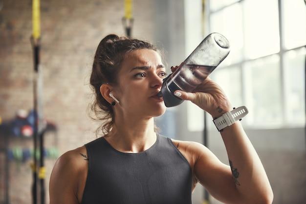イヤホンで若い運動女性のクローズアップは、ジムで運動しながら水を飲んでいます