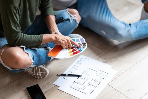 바닥에 앉아 있는 동안 아파트 벽을 칠하기 위해 색상 팔레트에서 색상을 선택하는 젊은 매력적인 커플을 클로즈업하세요.