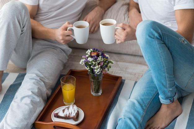Закройте молодых привлекательных гей-пар, сидящих на полу и пьющих кофе во время отдыха.