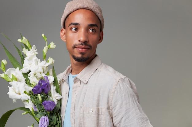 灰色の帽子と青いtシャツを着た若い魅力的な男のクローズアップ、彼の手に花束を持って、落ち着いた表情で離れて見て、赤い背景の上に立っています。
